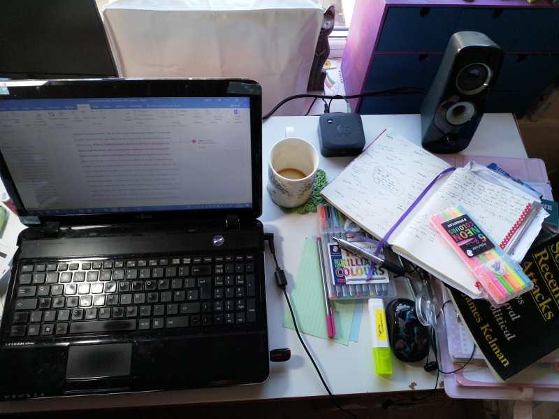 Photo of a messy desk with empty coffee mug and random ephemera