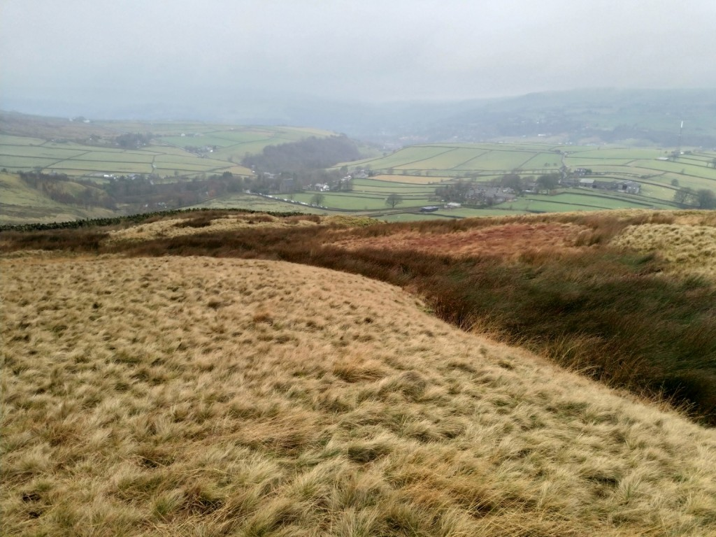 A landscape photograph of different fields, the landscape slopes down towards the market town of Todmorden.
