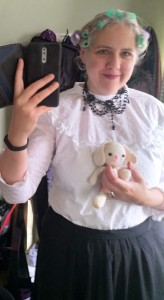 "An uncomfortable Jennie tries to take a rubbish selfie in the mirror while wearing the previous clothes. She is holding ""Blanche the Baum Rabbit"" crocheted for Sheffield Gothic."